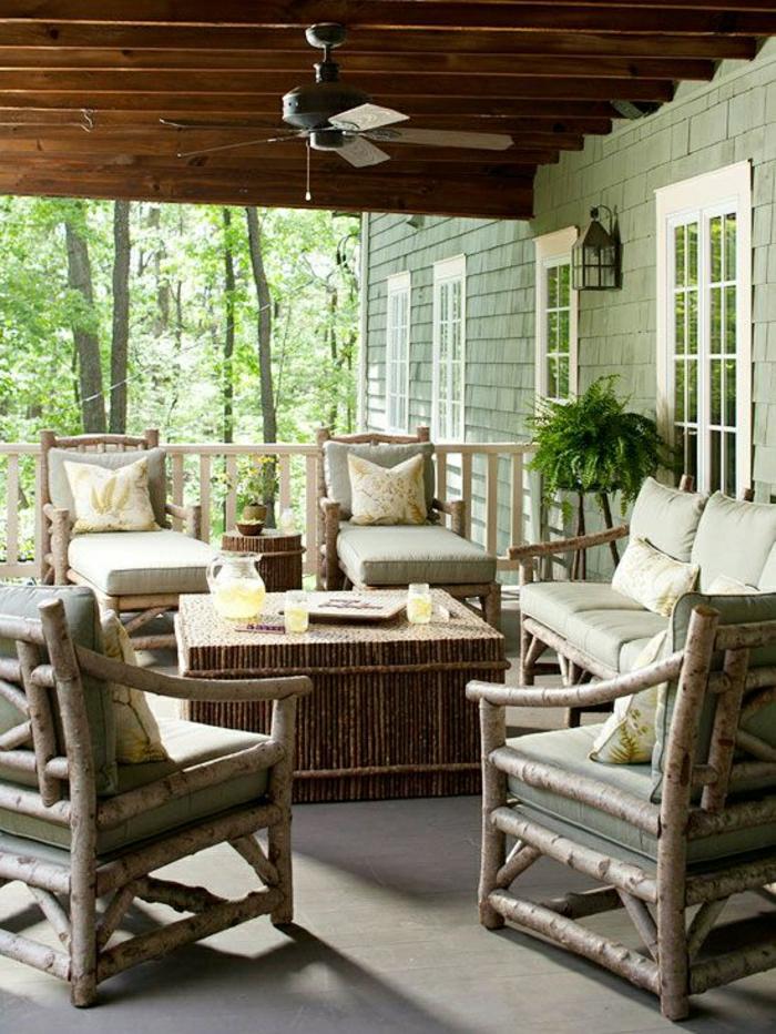 véranda-avec-chaises-en-bois-table-basse-en-bois-véntilateur-de-plafond-extérieur
