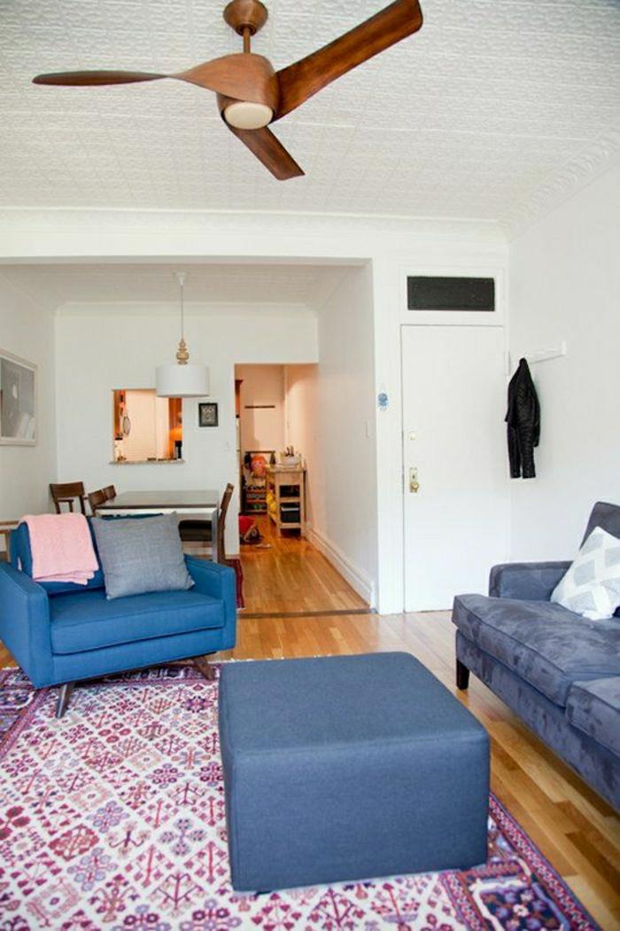 ventilateur-design-classique-en-bois-canapé-bleu-sol-en-parquet-murs-blancs-lustre-blanc-tapis-coloré