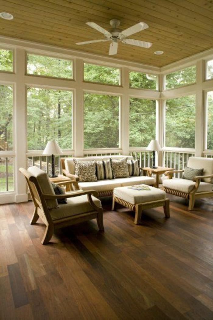 ventilateur-design-plafond-véranda-avec-fenetres-chaises-en-bois-canapés-en-bois-beiges