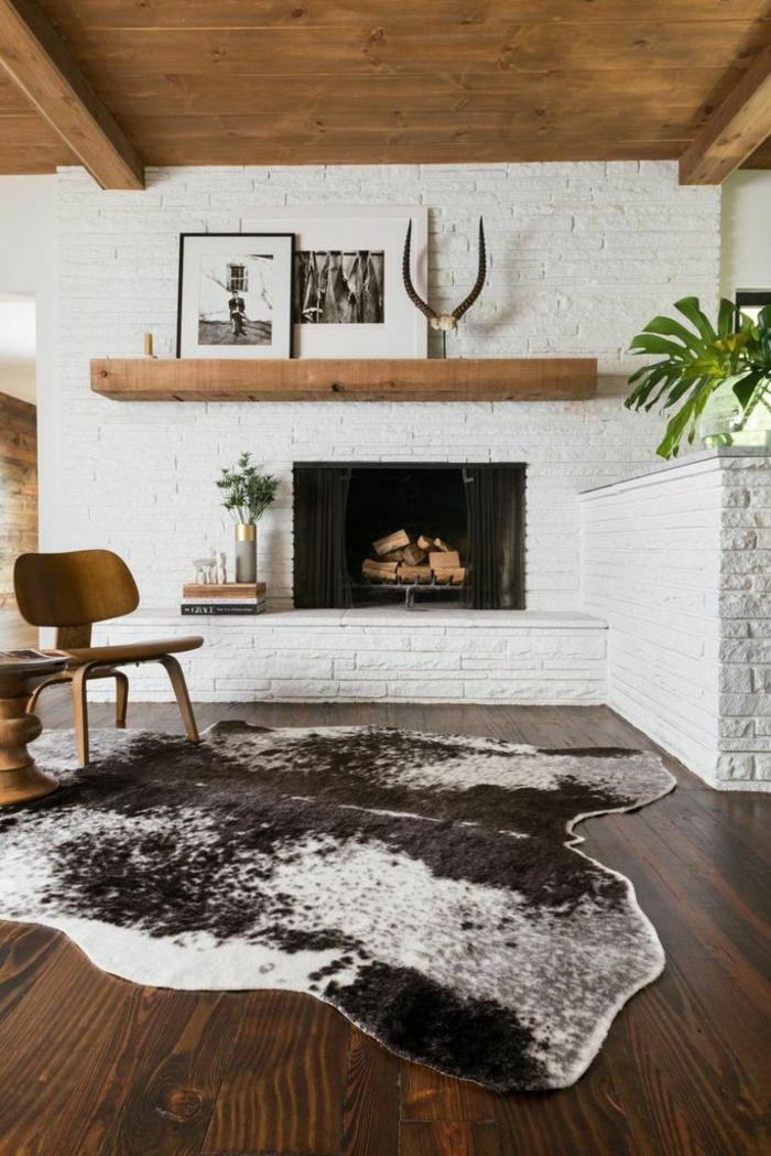0-salon-sol-parquet-foncé-cheminée-de-briques-blancs-chaise-en-bois-tapis-en-peau