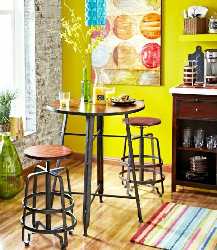 1-table-salle-a-manger-mur-jaune-mur-de-briques-fenetre-plein-de-lumière-tapis-coloré