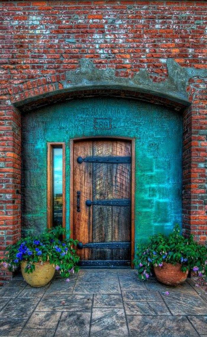 Porte-d-entrer-aigue-marine-couleur-fleurs-dans-vases-devant-l-entrée