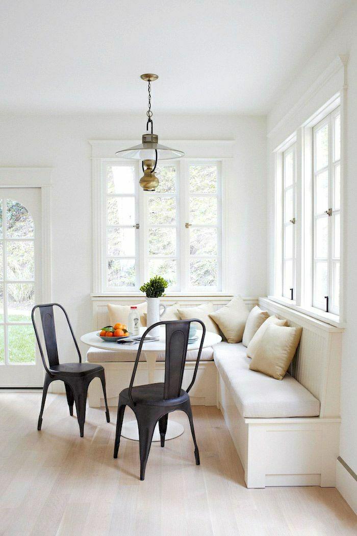 canapé-beige-table-tulipe-plastique-blanche-lustre-salle-de-séjour-moderne-chaise-noire