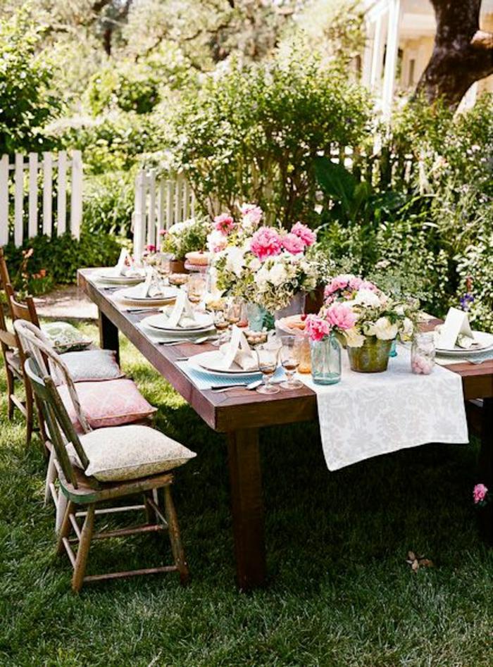 chemin-de-table-blanc-fleurs-sur-la-table-chaises-en-bois-de-jardin-set-de-table