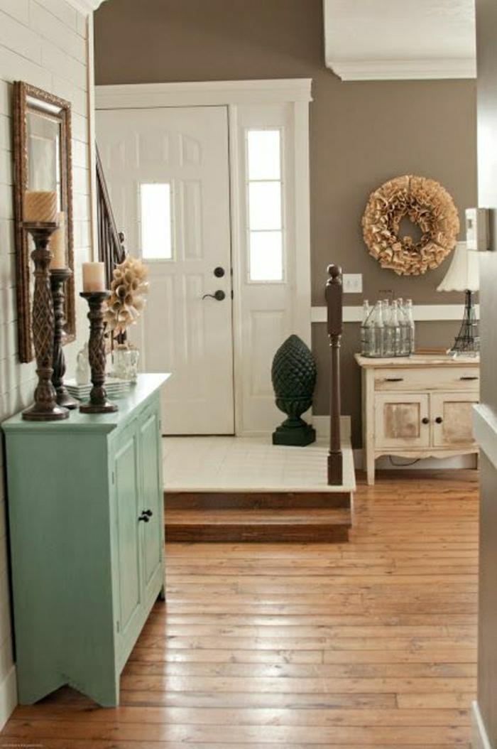 couloir-de-couleur-taupe-sol-en-plancher-en-bois-meuble-en-bois-bleu-porte-d-entrée-blanche