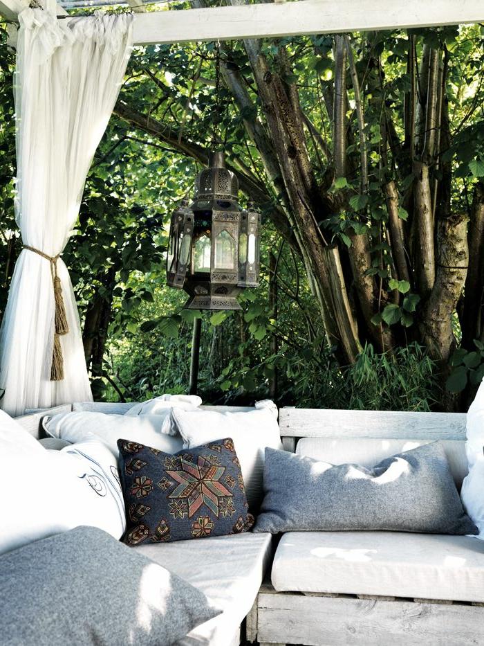 lampadaire-exterieur-maison-rustique-jardin-plantes-vertes-jardin-canapé-blanc-coussins