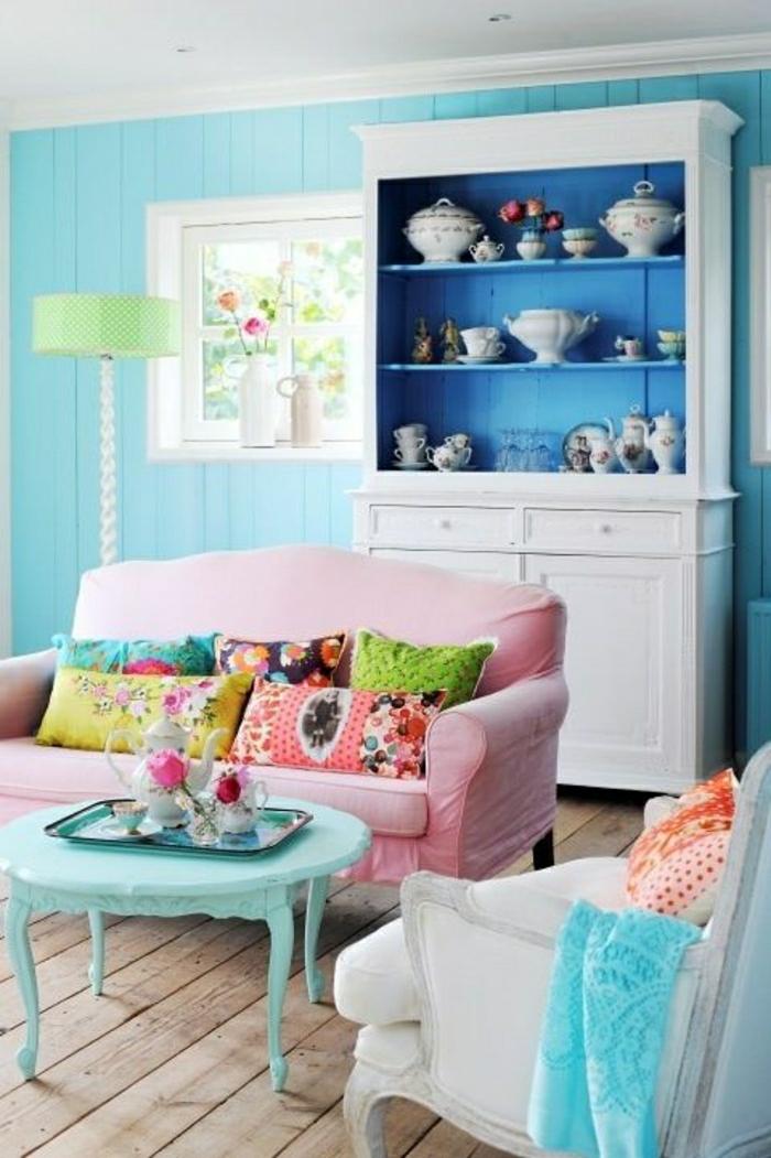 mur-plancher-bleu-ciel-canapé-rose-coussins-coloré-lampe-table-bleu-ciel-sol-en-plancher