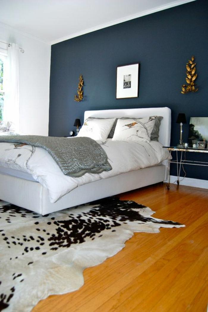 salle-de-coucher-sol-en-parquet-mur-bleu-foncé-lit-blanc-chambre-lumière