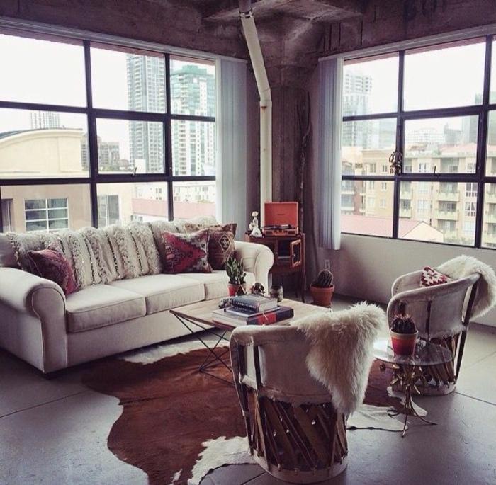 salon-ambiance-cocooning-tapis-en-peau-de-vache-sol-gris-mur-en-verre-fenetres-grandes