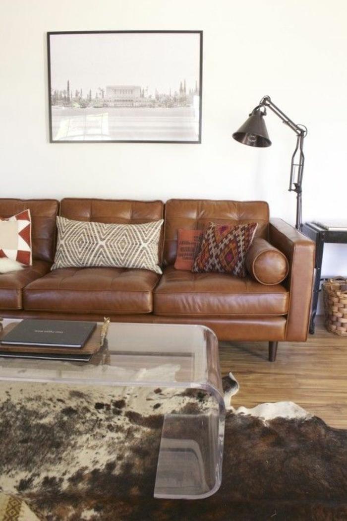 salon-avec-une-table-transparente-en-verre-canapé-en-cuir-marron-coussins-peintures-murales