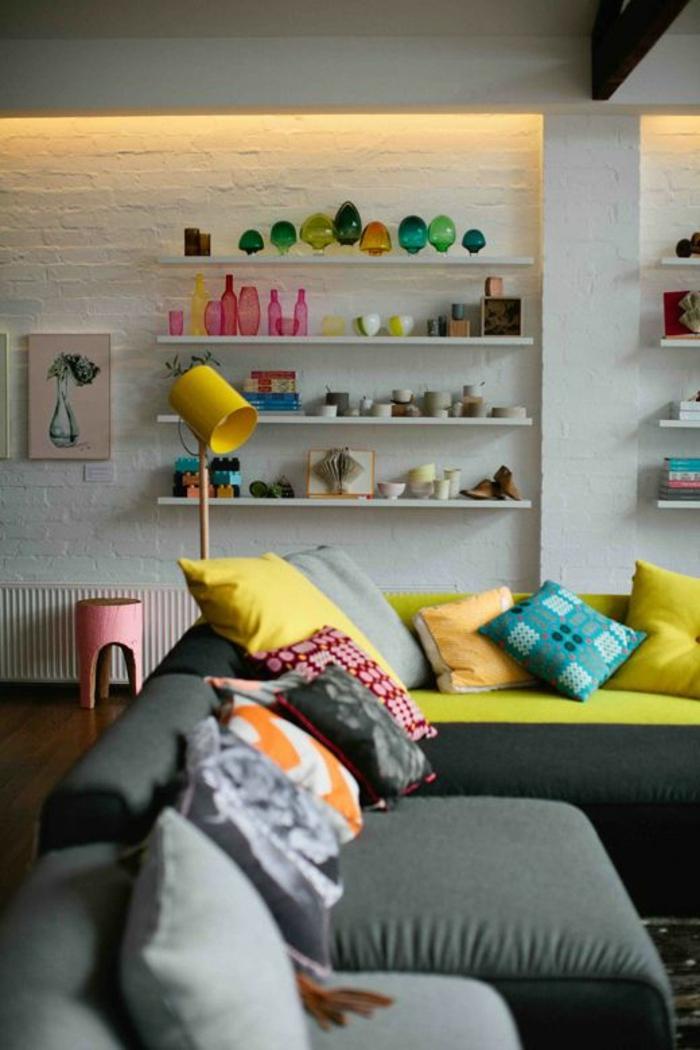 salon-moderne-coloré-étgère-bois-mur-blanc-de-briques-blancs-canapé-gris-peinture-murale