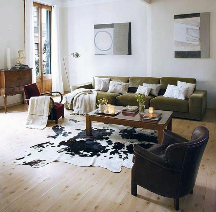 salon-sol-avec-tapis-en-peau-de-vache-parquet-canapé-vert-coussins-intérieur