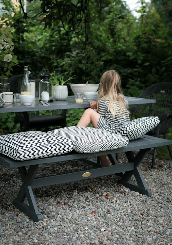 table-de-picnic-en-fer-gris-enfant-blonde-fille-manger-jardin-table-cailloux
