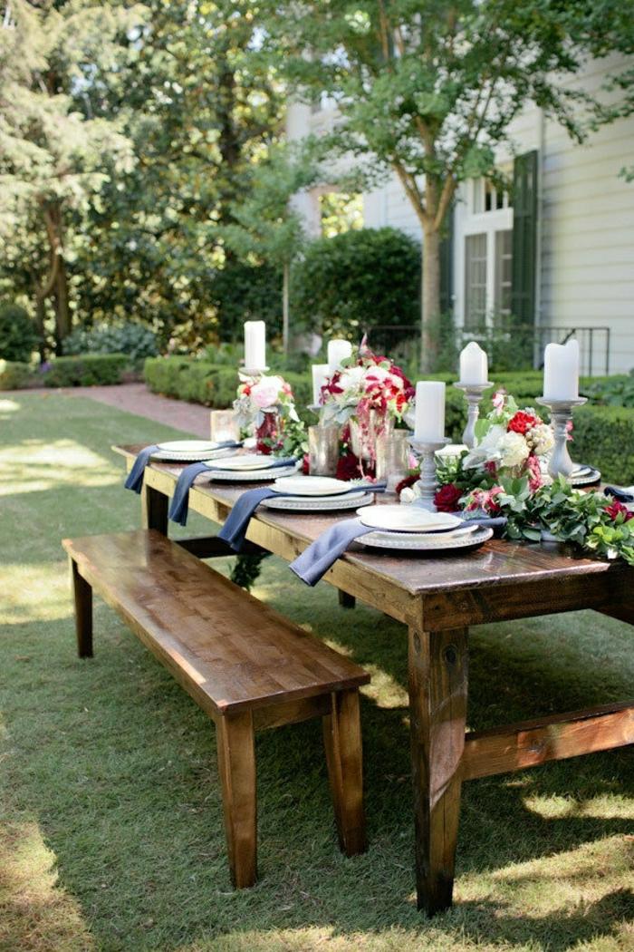 table-de-picnic-pelouse-vert-assiette-fleurs-sur-la-table-en-bois-décoration-de-table
