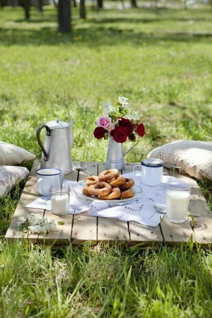 table-de-picnic-pelouse-vert-fleurs-sur-la-table-en-bois-jardin-ensoleilé