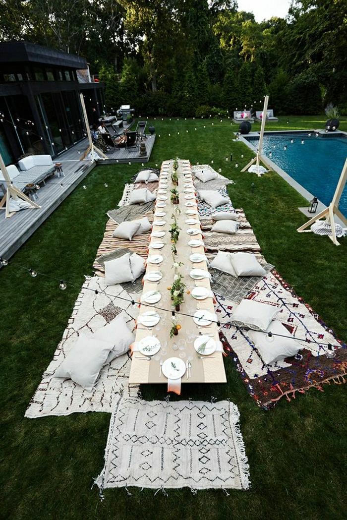 table-de-picnic-pelouse-vert-une-grande-table-en-bois-coussins-blanc-idée