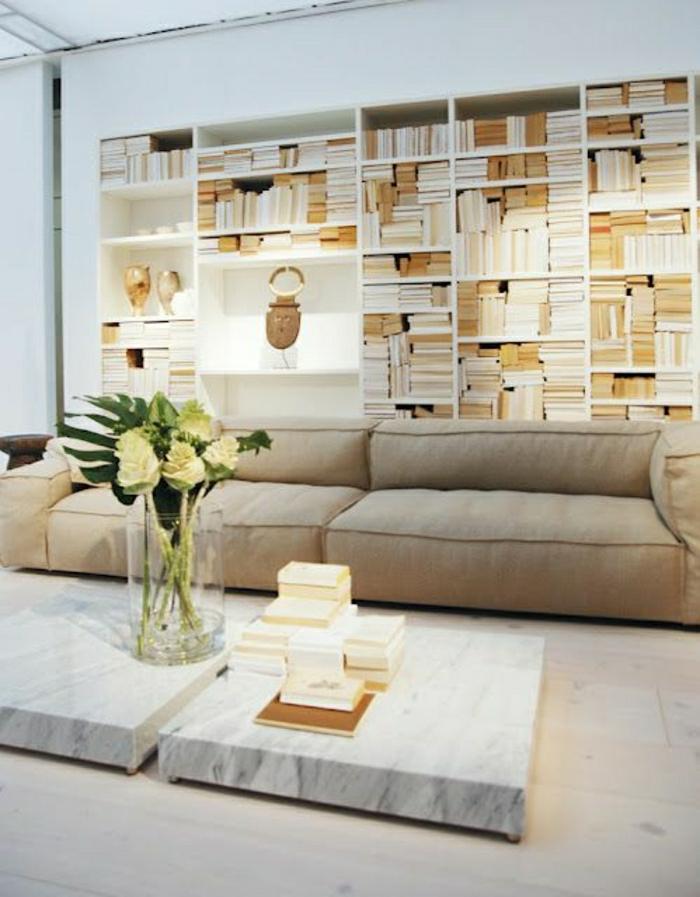 table-de-sol-en-marbre-blanc-canapé-beige-fleurs-sur-la-table-étagère-murale-en-bois