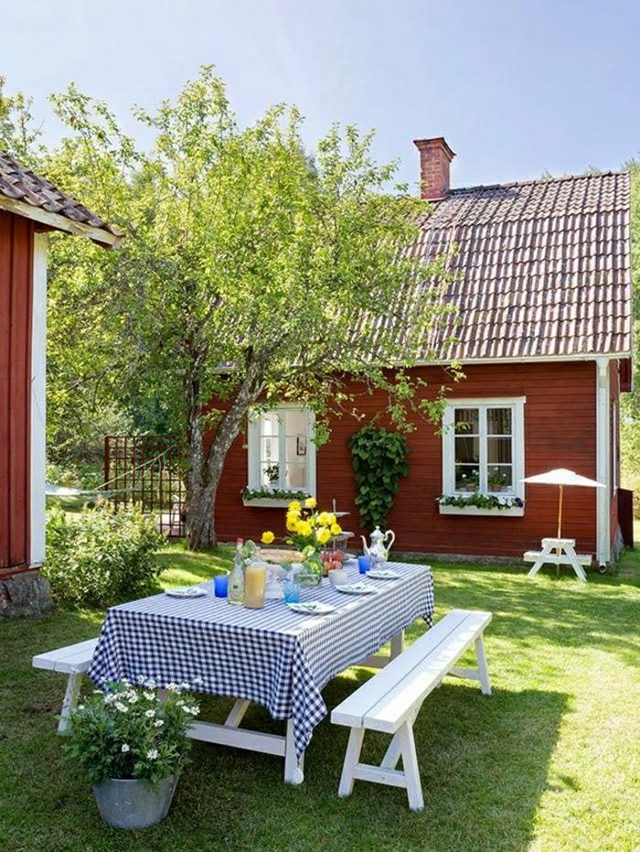 table-en-bois-blanc-banc-nappe-blanc-bleu-fleurs-sur-la-table-pelouse-verte