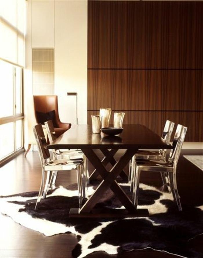 tapis-en-peau-de-vache-parquet-foncé-table-en-bois-chaises-transparentes-déco-brun
