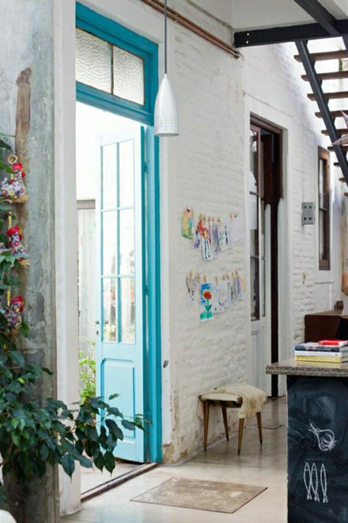 une-belle-porte-d-entrée-bleu-plante-verte-sol-beige-cuisine-mderne-mur-blanc-de-briques