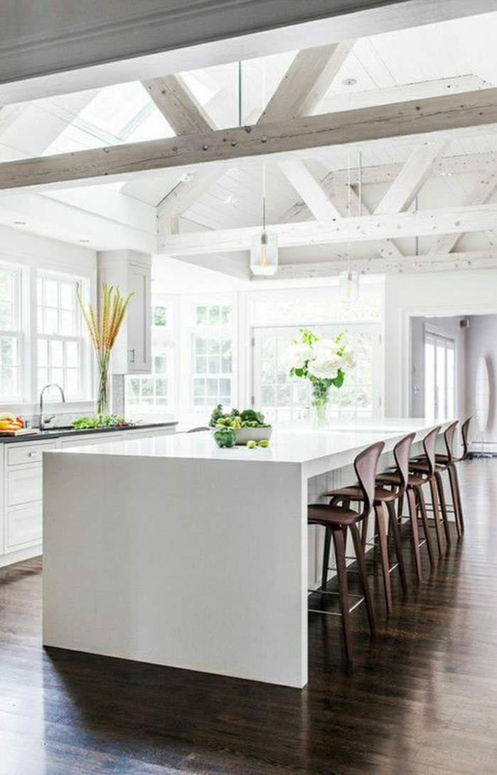 vaste-cuisine-avec-chaise-de-bar-en-bois-haut-bar-blanc-fleurs-lustre-fenetre-grande