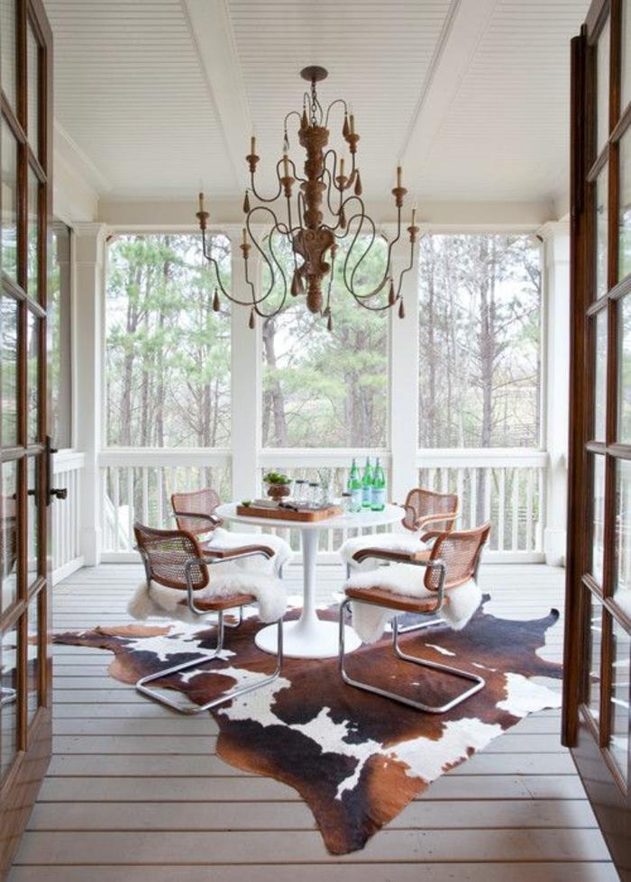 veranda-avec-tapis-de-peau-animal-sol-en-planchers-belle-vue-extérieur