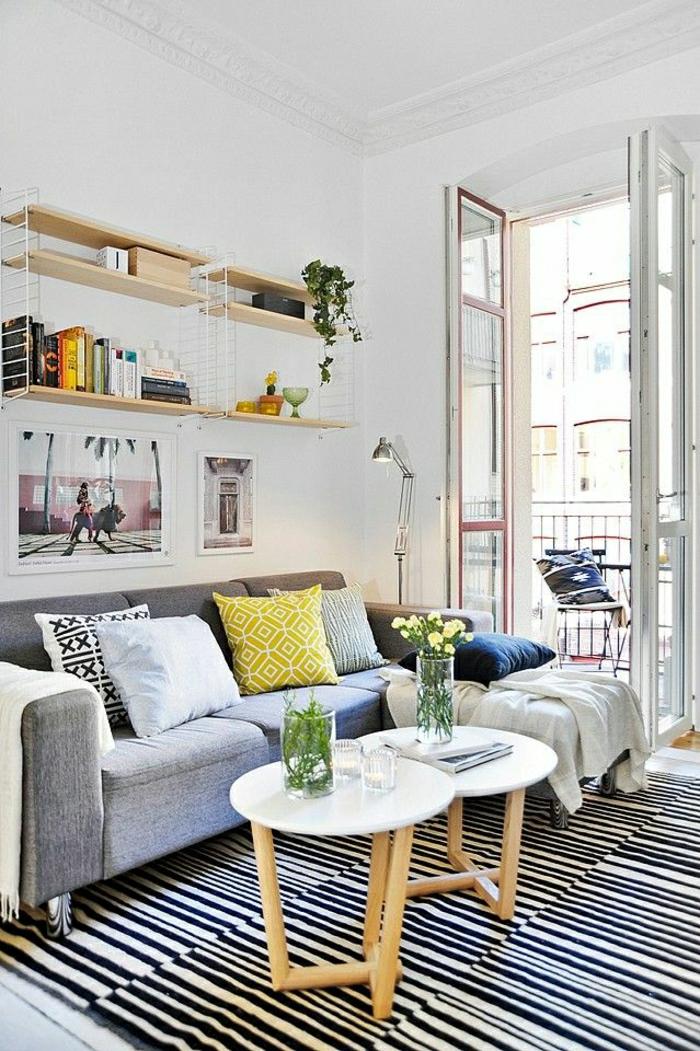 1-petite-table-basse-ronde-blanc-tapis-à-rayures-blanc-noir-coussins-colorés-canapé-gris