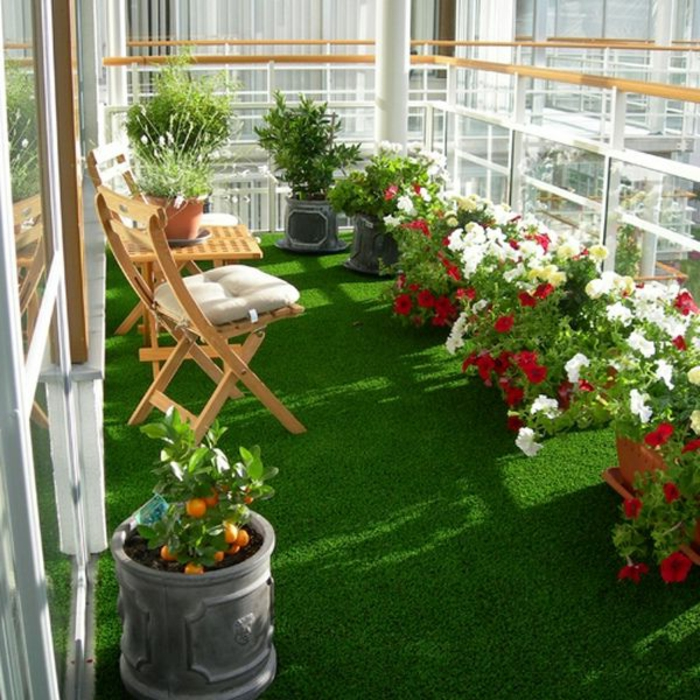 1-un-joli-balcon-avec-gazon-synthétique-pelouse-verte-fleurs-pour-le-balcon-chaises-en-bois