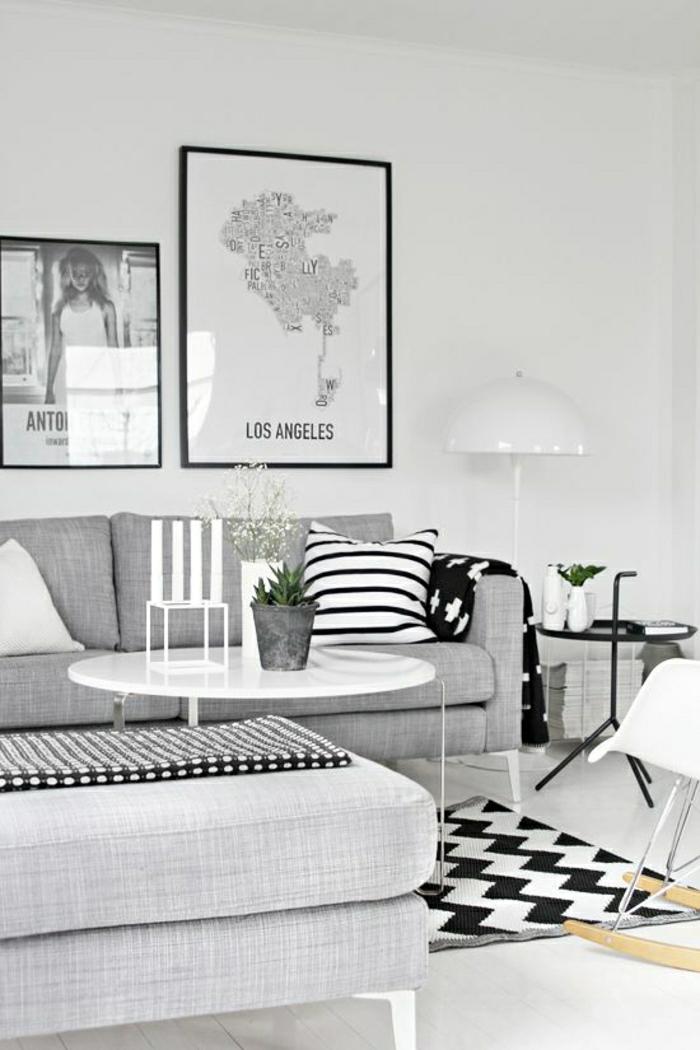 jolie-table-basse-ronde-blanche-plante-verte-peintures-murales-mur-blanc-coussins-blanc-noir
