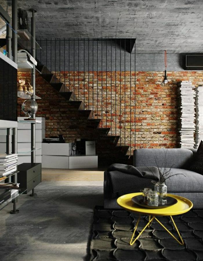 petite-table-basse-en-fer-jaune-sol-en-parquet-tapis-gris-canapé-noir-murs-de-briques