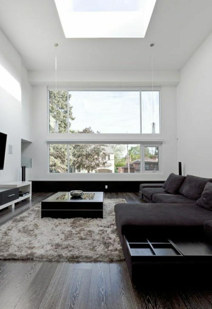 petite-table-basse-noire-sol-en-parquet-tapis-beige-gris-canapé-noir-murs-blancs-salon-moderne