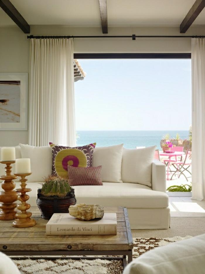 petite-table-basse-pour-le-salon-avec-fenetre-grande-belle-vue-vers-la-mer-rideaux-longs