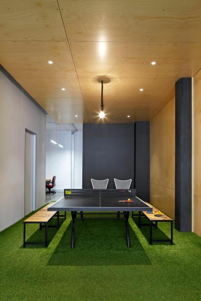 salle-sportive-avec-sol-en-gazon-synthetique-plafond-en-bois-lustre-tenis-de-table