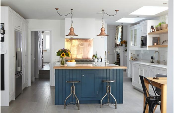 suspensions cuivre et tabourets industriels dans une cuisine blanche