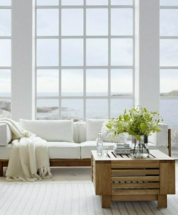 table-basse-en-bois-table-carrée-fleurs-sur-la-table-en-bois-canapé-blanc-fenetre-grande