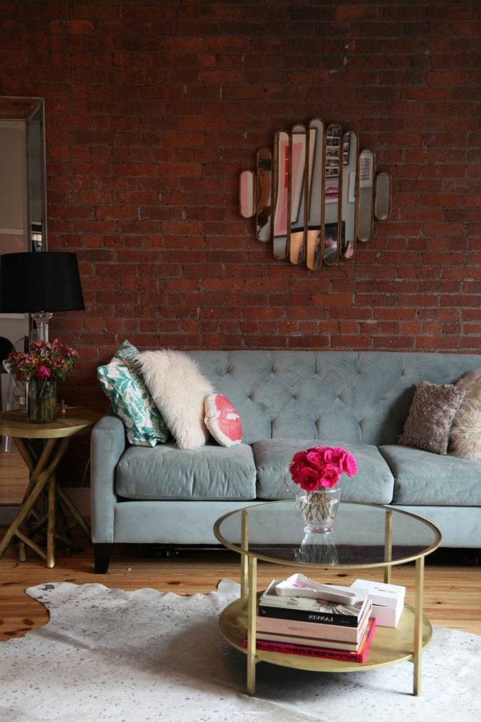 table-basse-ronde-sofa-gris-mur-briques-et-miroir-décoratif