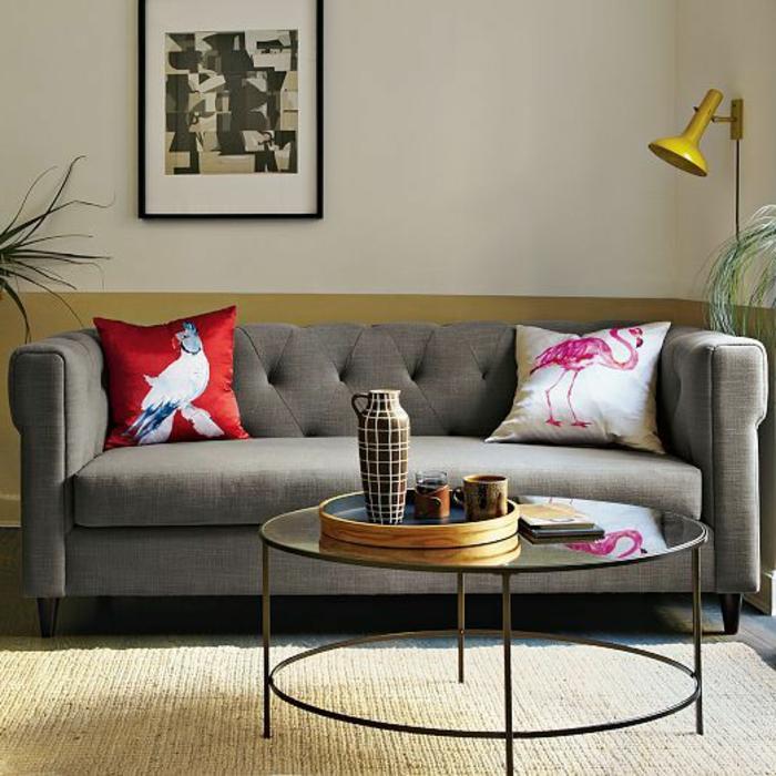 table-basse-ronde-verre-et-acier-près-d'un-sofa-gris