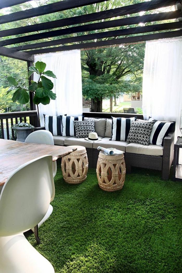 tapis-de-gazon-synthétique-de-couleur-vert-canapé-beige-coussins-blanc-noir-a-rayures