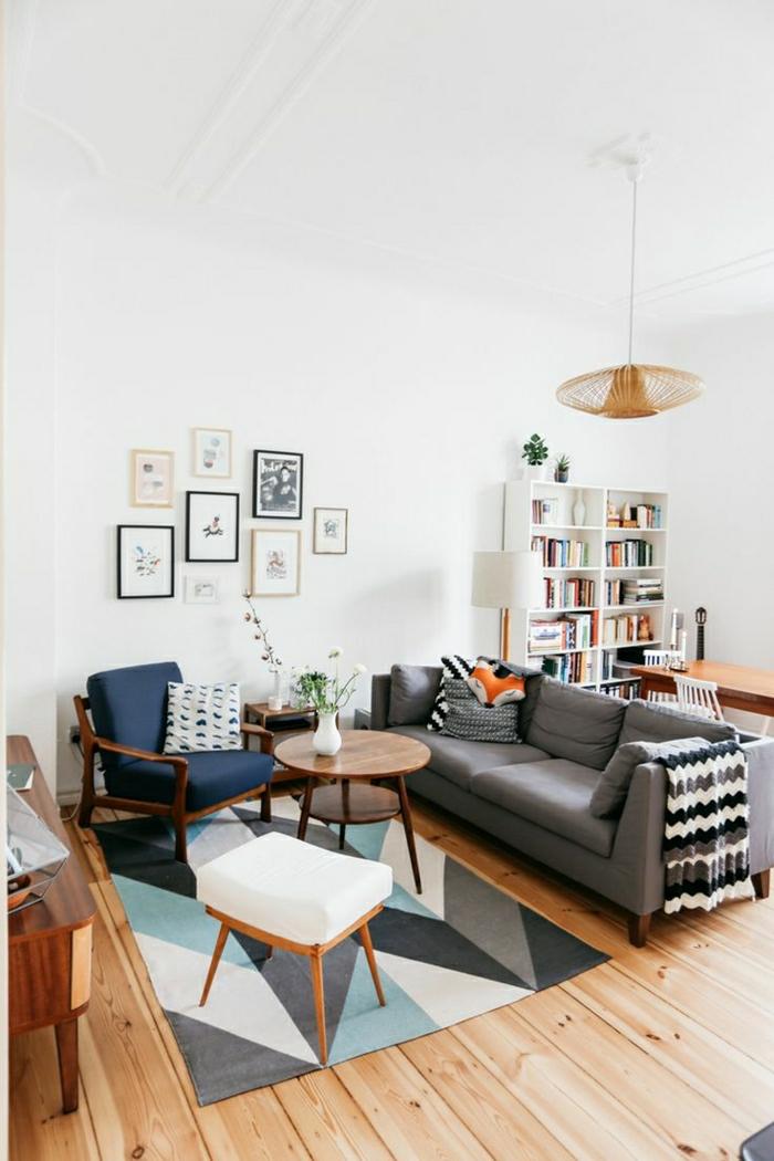 un-joli-tapis-coloré-petite-table-basse-en-bois-canapé-gris-coussins-colorés-mur-blanc