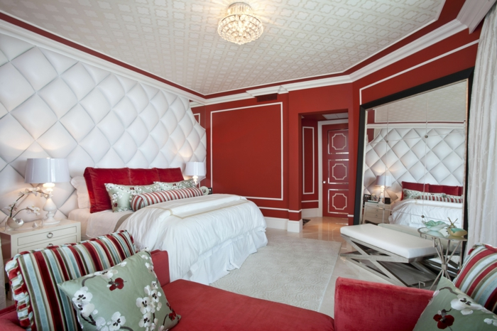 une-belle-chambre-à-coucher-de-couleur-carmin-linge-de-lit-blanc-coussin
