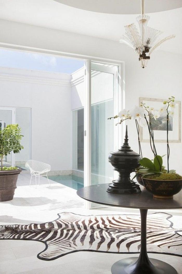 1-un-intérieur-blanc-tapis-à-rayures-blanches-noirs-plantes-vertes-vaste-maison-avec-piscine
