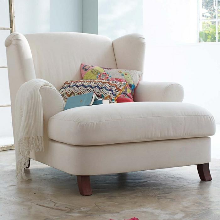 aménagement-petit-espace-avec-le-fauteuil-convertible-lit-chaise-confort-blanc-coussins-livre