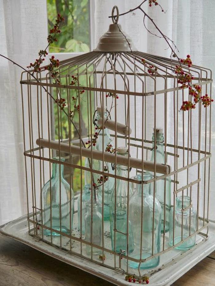 cage-à-oiseaux-décorative-remplie-de-bouteilles-turquoises