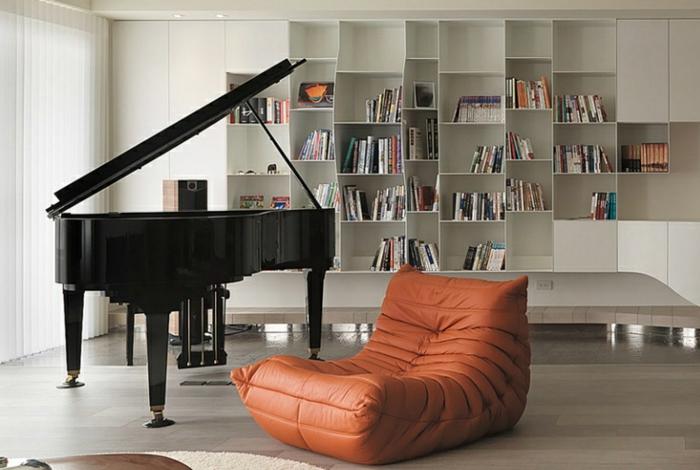 canapé-togo-marron-un-piano-noir-et-étagère-murale