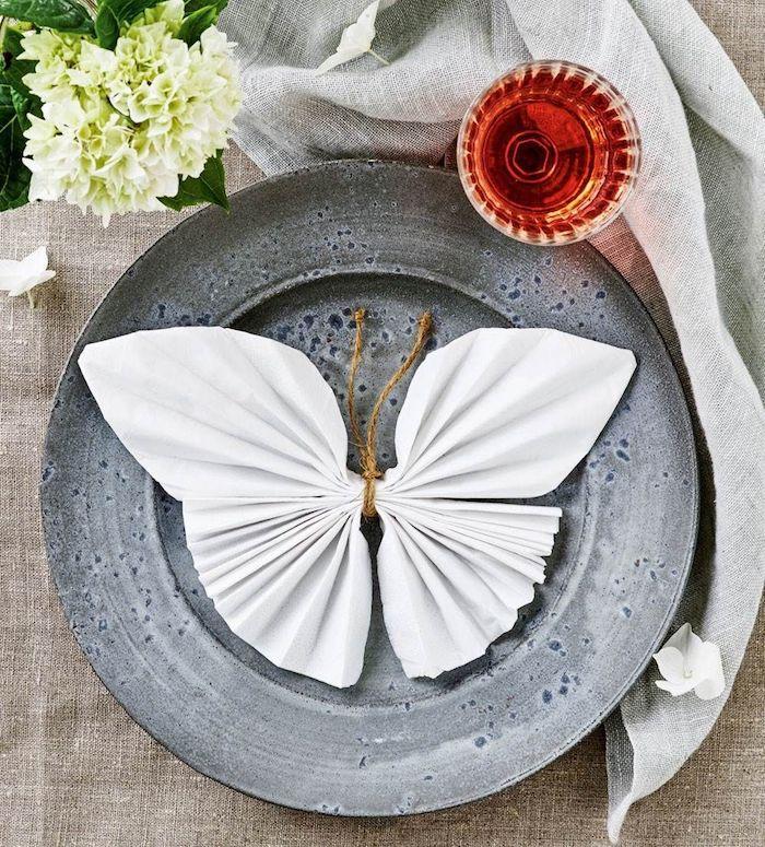 pliage serviette facile en forme de papillon blanc, idee pliage serviette en papier blanc avec ficelle pour nouer le centre