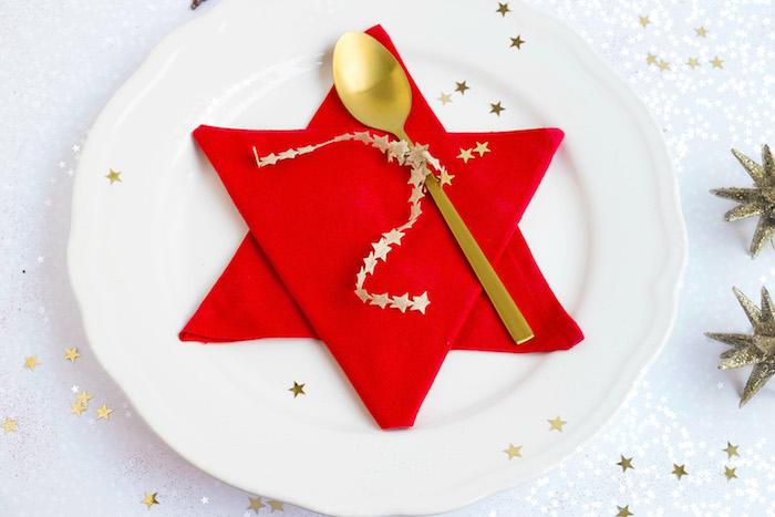 modele de pliage serviette etoile super simple réalisé avec deux serviettes de tissu rouges pliées en triangle