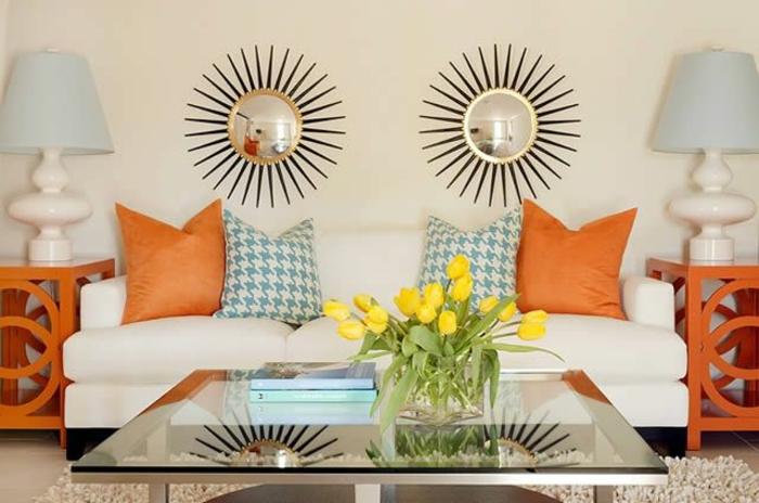 décoration-murale-avec-miroir-décoratif-canapé-blanc-avec-coussins-oranges-fleurs-sur-la-tabe-en-verre