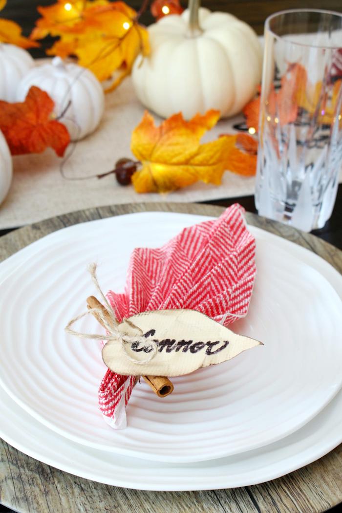 pliage serviette en papier simple en forme de feuille morte avec deco de feuille et baton de cannelle dans assiette blanche