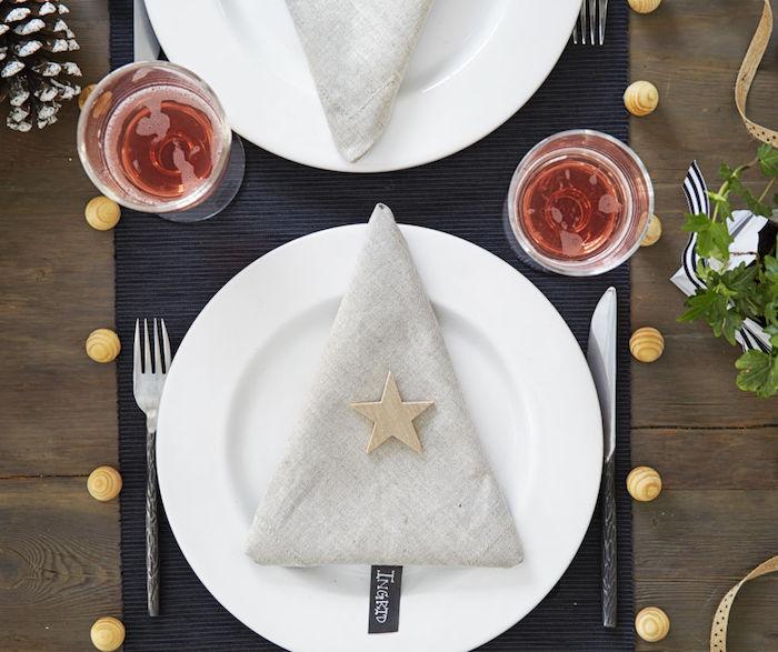 modele pliage serviette noel en forme de sapin de noel dans tissu gris dans assiette blanche, deco table noel