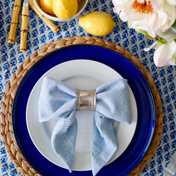 deco table de noel originale avec noeud de papillon bleu clair dans serviette de tissu serrée d un rond de serviette argenté